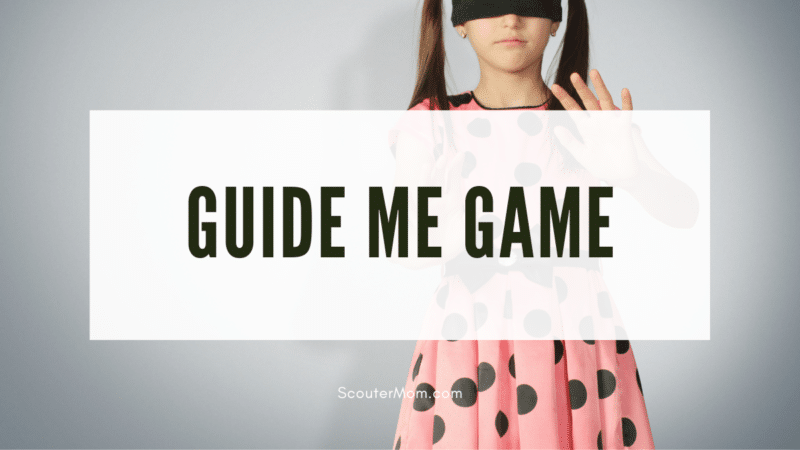 A girl with a blindfold on reaching out, indicating that this Guide Me game is a blindfolded game.