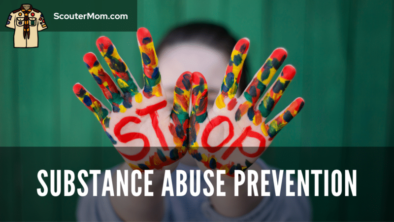 """A youth holding up hands with the word """"Stop"""" and colorful paint, to indicate the need for substance abuse prevention programs"""