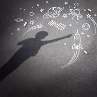 Child space dream as a childhood imagination concept with a cast shadow of a kid dreaming of being an astronaut or astronomy explorer with chalk drawings of a rocket spacecraft planets stars and a flying saucer.