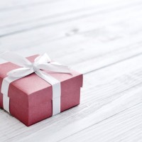 Red gift box with white ribbon over white wooden background